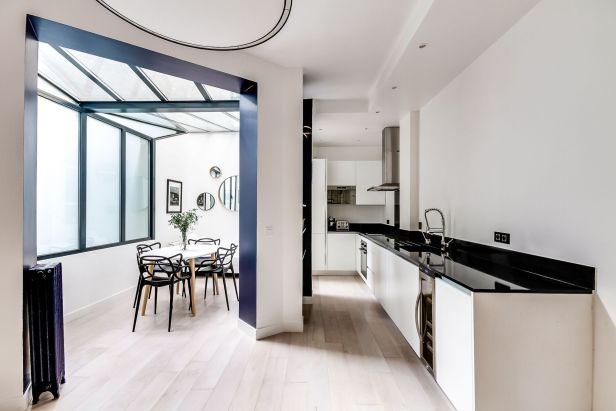 cuisine-lineaire-plan-de-travail-quartz-noir-veranda-avec-salle-a-manger-arche-bleu-nuit_5840815